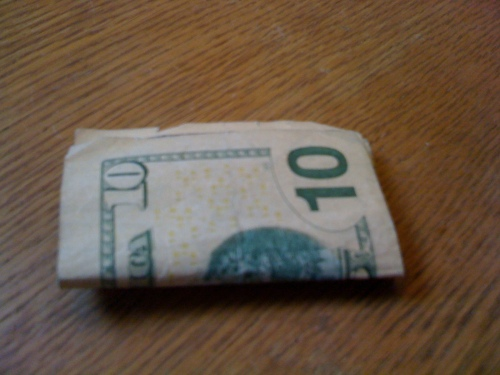 Photo of ten dollar bill, folded up.