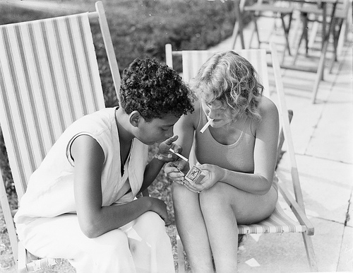 photo of women smoking a cigarette in the sun